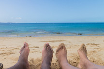 Two pairs of feet in the sand on the beach.