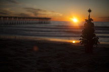 Christams tree on beach with waves and pier in background at sunset.