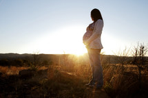 pregnant woman holding her belly in a sunburst