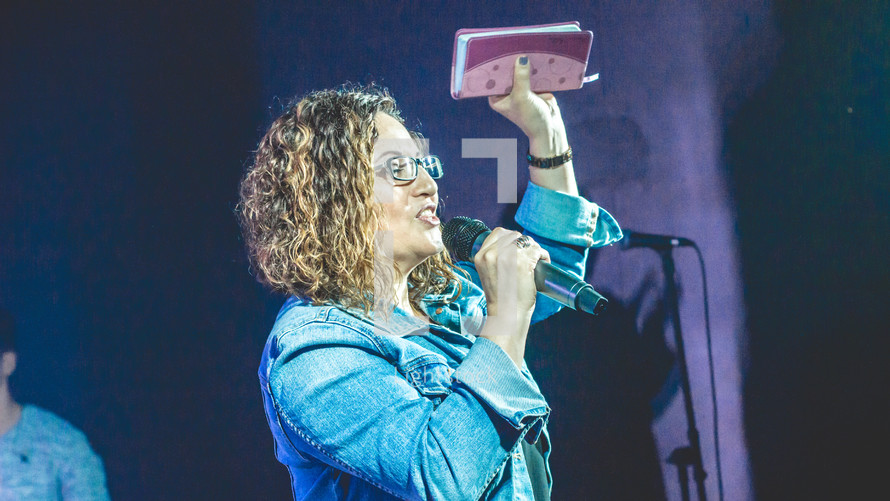 a woman holding a microphone and a raised Bible during a worship service