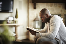 An African American man reads the Bible during his quiet time
