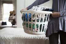 a woman holding a basket of dirty laundry