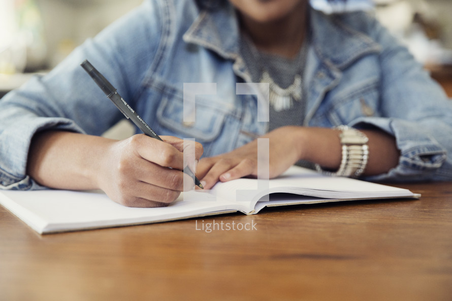 an African American woman sitting at a table writing in a journal
