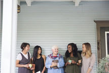 woman's group Bible study on a porch standing together holding Bibles