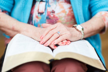mature woman with hands on a Bible
