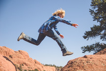 boy child leaping across rocks