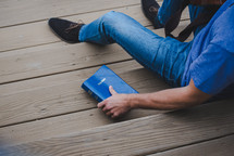 young man sitting on wooden steps next to a Bible