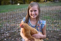 a little girl holding a chicken