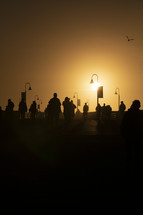 silhouettes of people on a pier at sunset