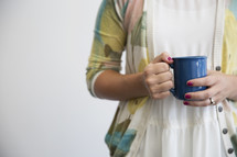 A woman in a sweater holding a blue coffee cup.