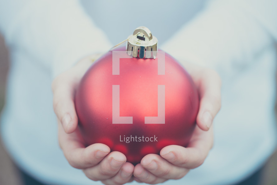an large red ornament in a man's hands