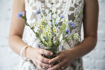 Woman holding bouquet of wildflowers.