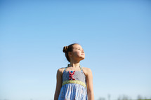 portrait of a girl standing against a blue sky