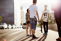 teenagers talking and holding a skateboard