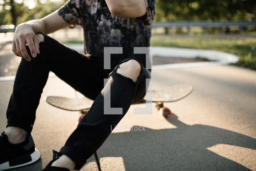 teen boy sitting on a skateboard