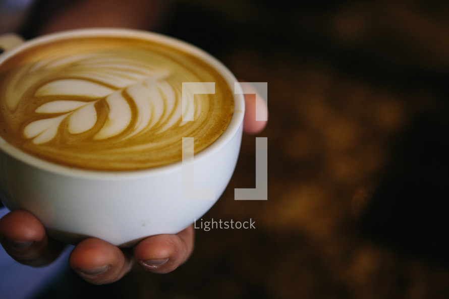 Hand holding a cup of latte with a leaf design.