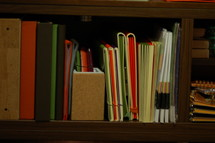 Bookshelf with books and binders.