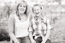 Mother and young son sitting laughing  portrait black and white