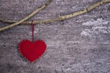 a felt heart ornament hanging on a branch