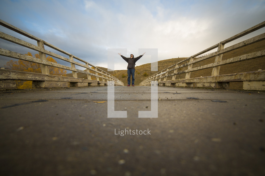 man standing on a bridge with hands raised to God