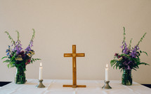 cross, candle, and flowers on an altar