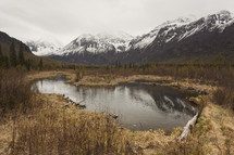mountain pond surrounded by snow capped mountains