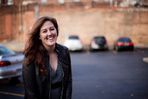 a smiling woman standing in a parking lot