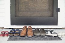 row of a families shoes on a door mat