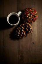 coffee cup, pine cone, and berries on a wood table