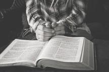 a teen girl praying near an open Bible