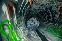 Man sitting in a sewer drain pipe painted with graffiti.