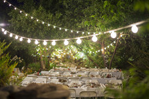 strand of glowing lights over folding chairs at an outdoor wedding
