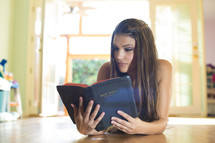 A young woman reading a Bible.