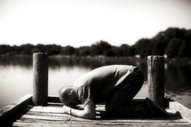 Man kneeling in prayer on river dock