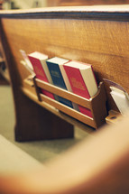 Bible and Hymnal in the back of a church pew