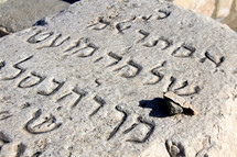Hebrew letters carved into a grave stone.