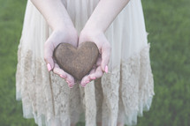 a woman holding a heart shaped stone in cupped hands