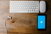 computer keyboard, mouse, earbuds, and cellphone with twitter app