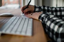 a man taking notes sitting at his computer