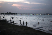 people on the beach at dusk