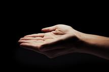 open hands under light.