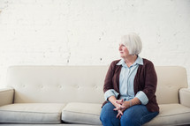 a woman sitting on a couch waiting