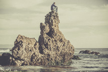 A man sitting on a rock formation in the ocean.