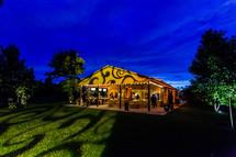 lights on an outdoor  wedding reception  pattern on barn blue sky sunset