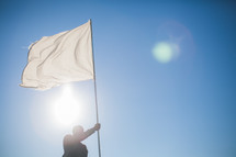 A man carrying a white flag of surrender
