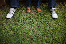 feet of a father and son in grass
