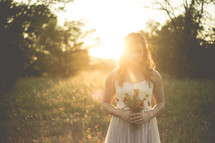 woman in a sundress holding flowers