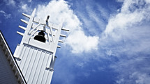 Clouds form over a bell tower or steeple of a church