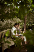 A Married couple reading the Bible in a park.