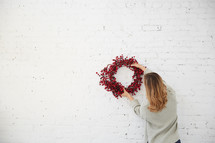 a woman standing with a red berry Christmas wreath
